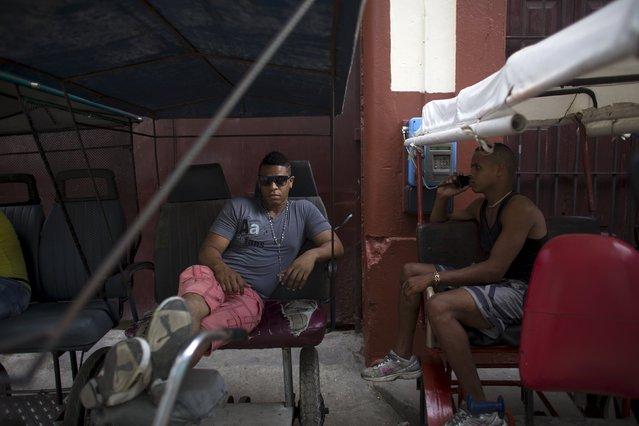 Pedicab driver Braison Navarro (L), 24, rests in his vehicle in downtown Havana, April 18, 2015. (Photo by Alexandre Meneghini/Reuters)