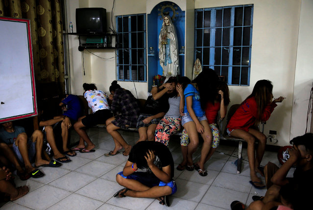 """Youths cover their faces at a police station during the """"Rid the Streets of Drinkers and Youth"""" operation in Las Pinas city, metro Manila, Philippines June 1, 2016. (Photo by Romeo Ranoco/Reuters)"""