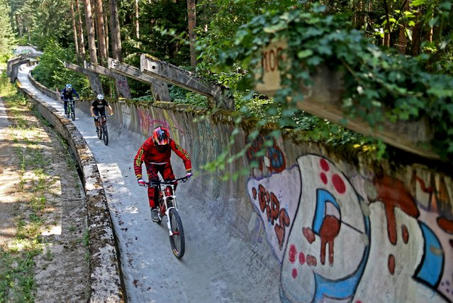 Downhill bikers Kemal Mulic (R-L), Tarik Hadzic and Kamer Kolar train on the disused bobsled track from the 1984 Sarajevo Winter Olympics on Trebevic mountain near Sarajevo, Bosnia and Herzegovina, August 8, 2015. (Photo by Dado Ruvic/Reuters)