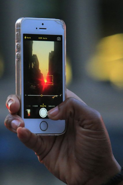 """A man takes a picture of a sunset, during the bi-annual occurrence """"Manhattanhenge"""" in New York July 11, 2014. Manhattanhenge, coined by astrophysicist Neil deGrasse Tyson, occurs when the setting sun aligns itself with the east-west grid of streets in Manhattan, allowing the sun to shine down all streets at the same time. (Photo by Eduardo Munoz/Reuters)"""