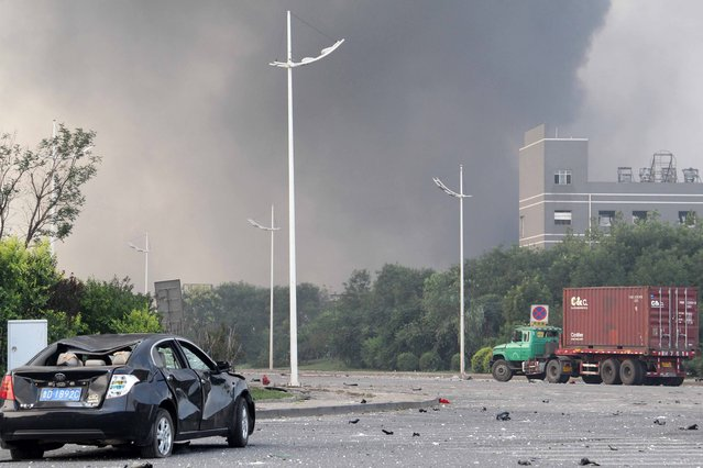 Damaged vehicles are seen as smoke rises from the site of a series of explosions in Tianjin on August 13, 2015. (Photo by AFP Photo)