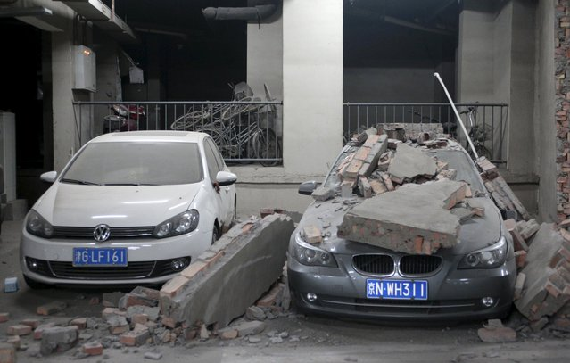 Damaged cars and a broken wall are pictured inside the parking lot of a building where residents were evacuated, near the site of Wednesday's explosions, at Binhai new district in Tianjin, China, August 13, 2015. (Photo by Reuters/Stringer)