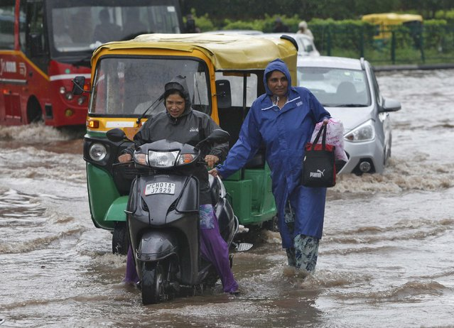 People commute through a flooded road after heavy rains in Chandigarh, India, June 28, 2016. (Photo by Ajay Verma/Reuters)