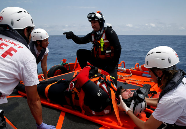 Rescue swimmers of the Migrant Offshore Aid Station (MOAS) and medical staff from Italian NGO EMERGENCY take part in a training exercise off the MOAS ship Topaz Responder, as the ship stands by for migrants in distress, in international waters off the coast of Libya, June 22, 2016. (Photo by Darrin Zammit Lupi/Reuters)
