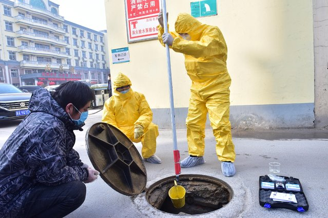 Workers of the ecology and environment bureau collect samples from the sewage system of a hospital in Xinle, Hebei province, February 8, 2020. (Photo by Reuters/China Daily)