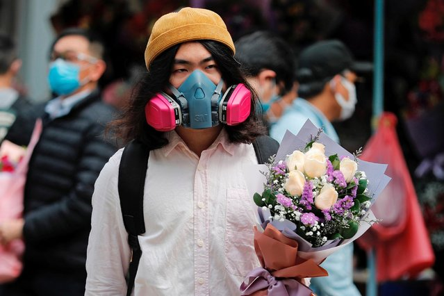A man wears a gas mask as he holds a bouquet of flowers, following the outbreak of the novel coronavirus on Valentine's Day in Hong Kong, China on February 14, 2020. (Photo by Tyrone Siu/Reuters)