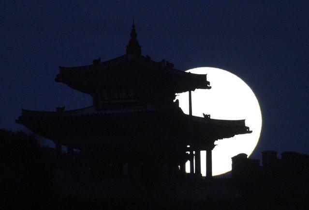 A supermoon rises behind Hwaseong Fortress in Suwon August 11, 2014. (Photo by Kim Hong-Ji/Reuters)