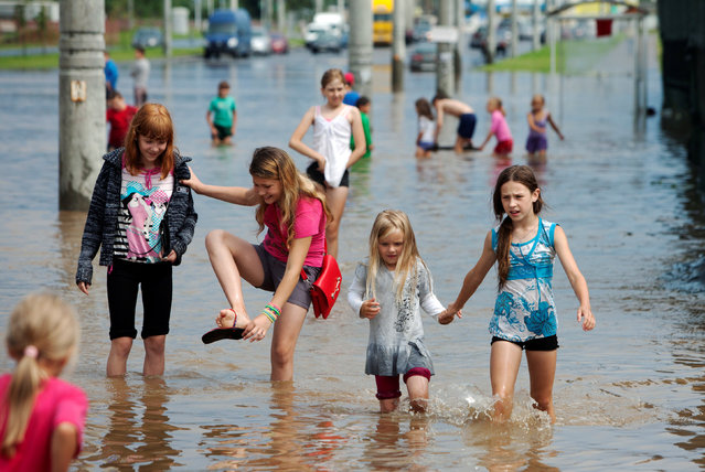 Children play on a flooded street after heavy rain in Minsk, Belarus July 13, 2016. (Photo by Vasily Fedosenko/Reuters)