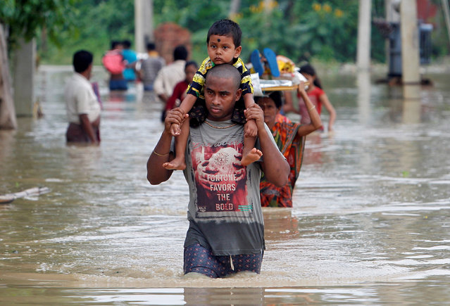 A man carries his child through a flooded area to a safer place after heavy rains at Baldakhal vallage on the outskirts of Agartala, India, September 3, 2017. (Photo by Jayanta Dey/Reuters)