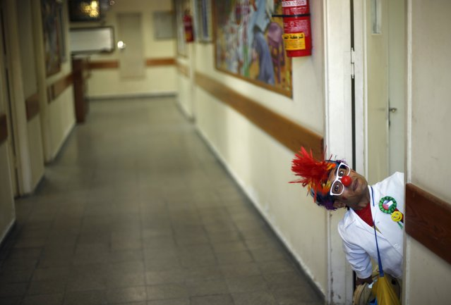 A Palestinian social activist working for the International South South Cooperation (Cooperazione Internazionale Sud Sud, or CISS) entertain children who are cancer patients, while dressed as a clown, inside a hospital in Gaza City August 31, 2015. Activists working for the Italian non-profit NGO use entertainment and humour to help bring treatment to children suffering from psychological trauma in the Gaza Strip. (Photo by Mohammed Salem/Reuters)