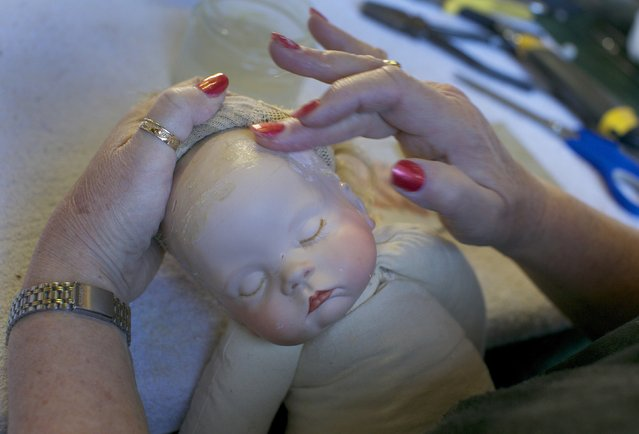 Doll restorer Kerry Stuart rubs a filling compound into the cracked head of a plastic doll at Sydney's Doll Hospital, July 15, 2014. Opened in 1913, Sydney's Doll Hospital has worked on millions of dolls, teddy bears and other toys. (Photo by Jason Reed/Reuters)