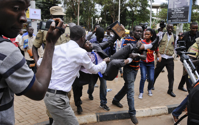 An activist opposed to the extension of presidential age limits is arrested and carried off by uniformed and plain-clothes police, while shouting for America and Israel to come to the rescue of Ugandans, near the Parliament building in Kampala, Uganda Thursday, September 21, 2017. Ugandan police on Thursday fired tear gas to disperse protesters and arrested dozens of people opposed to plans to introduce legislation that could allow the longtime president Yoweri Museveni to extend his rule. (Photo by Ronald Kabuubi/AP Photo)
