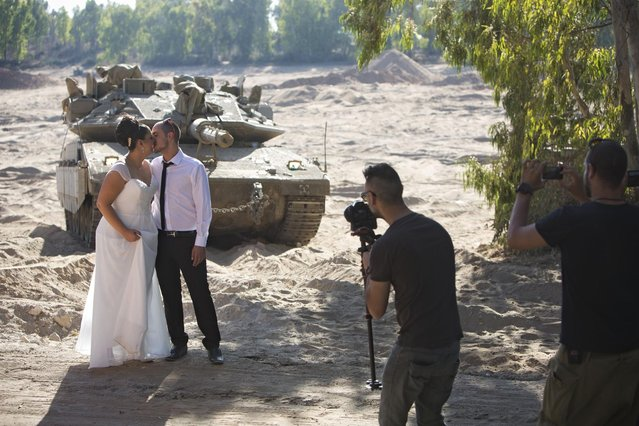Israeli couple Noga and Moshiko Siho have their wedding photo taken in an army staging area on the Israeli Gaza border, near Kibbutz Yad Mordechai, Israel, on August 27, 2014. (Photo by Oded Balilty/AP Photo)