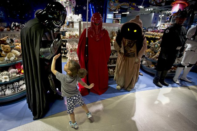 """A man dressed as Darth Vader from """"Star Wars"""" high fives a child as people arrive to purchase toys that went on sale at midnight in advance of the film """"Star Wars: The Force Awakens"""" in Times Square in the Manhattan borough of New York, September 4, 2015. (Photo by Carlo Allegri/Reuters)"""