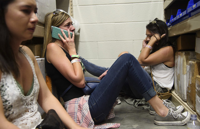 Women make phone calls while taking shelter inside the Sands Corporation plane hangar after a mass shooting in which dozens were killed at Route 91 Harvest Festival on Sunday, October 1, 2017, in Las Vegas. (Photo by Al Powers/Invision/AP Photo)