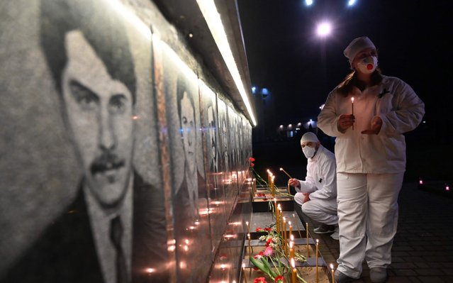 Chernobyl plant workers wearing face masks light candles at the monument to Chernobyl victims in Slavutich, the city where the power station's personnel lived, some 50 kilometres (30 miles) from the accident site on April 25, 2020 during a memorial ceremony amid the COVID-19 pandemic, caused by the novel coronavirus. Ukraine on April 26, 2017 marks the 34th anniversary of the Chernobyl disaster which was the world's worst nuclear accident. (Photo by Sergei Supinsky/AFP Photo)
