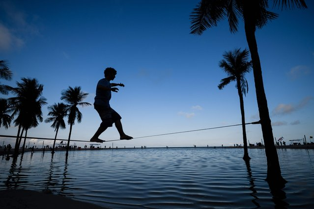 A man walks on a slackline between two palm trees on Copacabana beach in Rio de Janeiro, on 30 July 2016. The city is making last minute preparations for the events and celebrations as the 2016 Rio Olympic Games are set to begin in Rio on August 5 and run until August 21, 2016. (Photo by Leon Neal/AFP Photo)