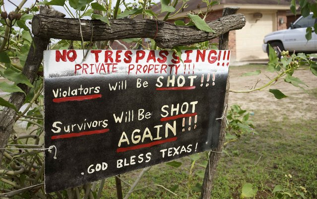 """A handmade sign to deter trespassers hangs in the front yard of Fernando Rivera Jr.'s house in Brownsville, Texas September 2, 2014. According to Rivera Jr, there is an open gate in the U.S.-Mexico border fence which immigrants would stroll through and onto the Rivera's property. The """"Patriots"""" are a heavily armed group who patrol the U.S. border with Mexico, trying to deter immigrants from crossing the border illegally. (Photo by Rick Wilking/Reuters)"""