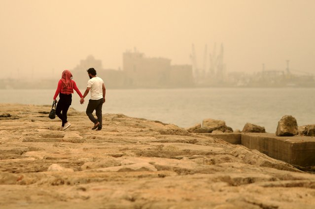 A couple walk during a sandstorm near the sea castle of the port-city of Sidon, Lebanon September 8, 2015. A heavy sandstorm swept across parts of the Middle East on Tuesday, hospitalising scores of people in Lebanon and disrupting air strikes and fighting in neighbouring Syria. Clouds of dust also engulfed Israel, Jordan and Cyprus where aircraft were diverted to Paphos from Larnaca airport as visibility fell to 500 metres. (Photo by Ali Hashisho/Reuters)