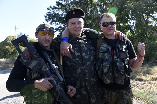 Armed pro-russian militants pose for the photographer as they take a break at a check point near a front line where shelling continues between pro-Russian forces and the Ukrainian army in the village of Olenivka some 30 kms south of Donetsk on the way to Mariupol, eastern Ukraine, on September 14, 2014.(Photo by Philippe Desmazes/AFP Photo)