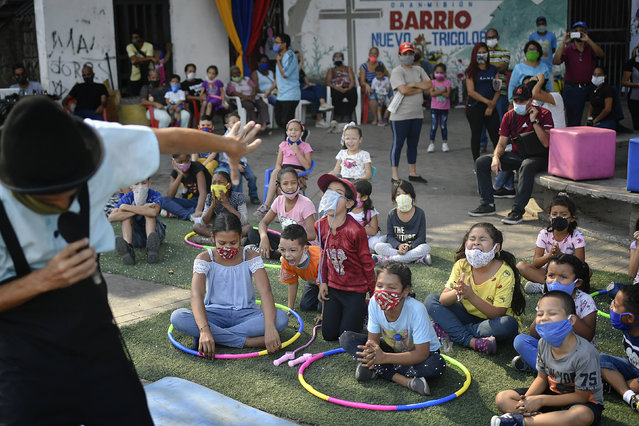Children watch a performance by the National Circus Foundation of Venezuela at the San Juan neighborhood of Caracas, Venezuela, Saturday, May 9, 2020. The circus also does live stream performances at the National Caracas theater during the lockdown to prevent the the spread of the new coronavirus. (Photo by Matias Delacroix/AP Photo)