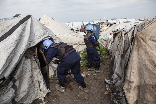 Members of the United Nations Police, UNPOL, search shelters for contraband in the Protection of Civilians (POC) site at the United Nations Mission in South Sudan (UNMISS) compound in Malakal, South Sudan on Friday, July 15, 2016. (Photo by Jane Hahn/The Washington Post)