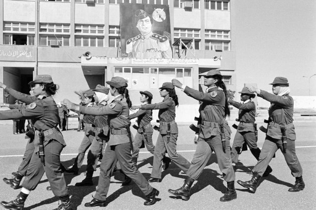Female soldiers with AK-47 rifles and bayonets march on the parade grounds at the Women's Military Academy in Tripoli, Libya, on January 18, 1986. At rear is a portrait of of Libyan ruler Moammar Gadhafi. (Photo by Giulio Broglio/AP Photo)