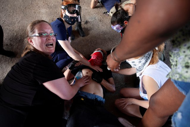 A protester, who was hit by an object fired by police, is aided by other protesters during a rally against the death in Minneapolis police custody of George Floyd, in Austin, Texas, U.S., May 30, 2020. (Photo by Nuri Vallbona/Reuters)