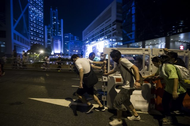Protesters push a traffic barrier to block the main street to the financial Central in Hong Kong September 28, 2014. Some Hong Kong financial firms advised staff to work from home on Monday or go to secondary offices after thousands of pro-democracy demonstrators blocked parts of the city and clashed with police. (Photo by Tyrone Siu/Reuters)