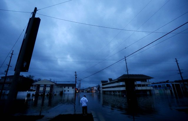 With nightfall approaching, Rodrigo Vargas, 25, of Seaside Heights, N.J., ponders treading through floodwaters to check on his second floor apartment. (Photo by Julio Cortez/Associated Press)