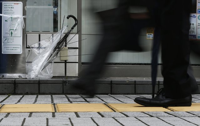 A broken umbrella is seen in front of a convenience store as pedestrians walk in a strong wind caused by Typhoon Phanfone on a street in Tsu, Mie Prefecture, western Japan October 6, 2014. (Photo by Yuya Shino/Reuters)