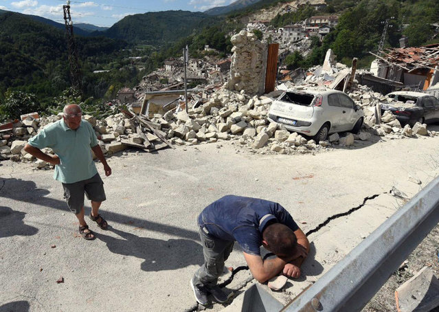 A man leans on a wall as the collapsed village of Pescara del Tronto, central Italy, is seen behind him, Wednesday, August 24 2016 following an earthquake. The magnitude 6 quake struck at 3:36 a.m. (01:36 GMT) and was felt across a broad swath of central Italy, including Rome where residents of the capital felt a long swaying followed by aftershocks. (Photo by Crocchioni/ANSA via AP Photo)