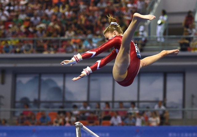 Switzerland's Ilaria Kaeslin performs on the uneven bars during the women's qualification at the Gymnastics World Championships in Nanning, in China's southern Guangxi province on October 5, 2014. (Photo by Greg Baker/AFP Photo)