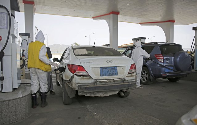 Yemeni attendants wearing personal protective equipment pump fuel at a petrol station amid fuel shortages in Sanaa, Yemen, Monday, June 15, 2020. (Photo by Hani Mohammed/AP Photo)
