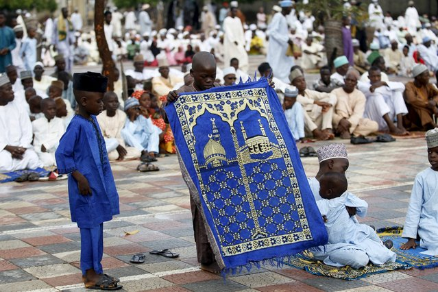 A boy spreads a pray mat before the start of Islamic prayers marking the Eid al-Adha festival, outside the Kofar Mata district mosque in the city of Kano, Nigeria, September 24, 2015. (Photo by Akintunde Akinleye/Reuters)