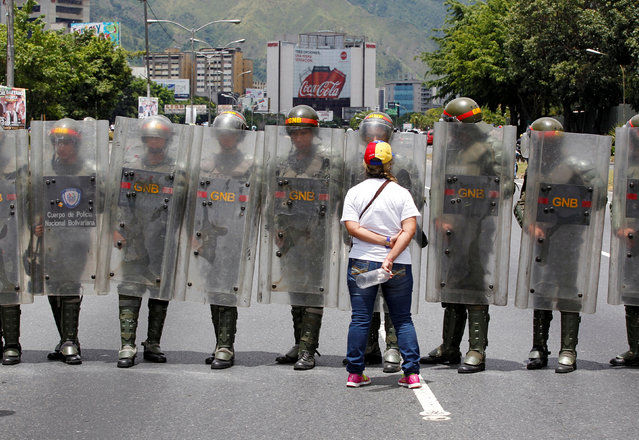 A woman looks on as police officers block the street while opposition supporters take part in a rally to demand a referendum to remove Venezuela's President Nicolas Maduro, in Caracas, Venezuela, September 1, 2016. (Photo by Christian Veron/Reuters)