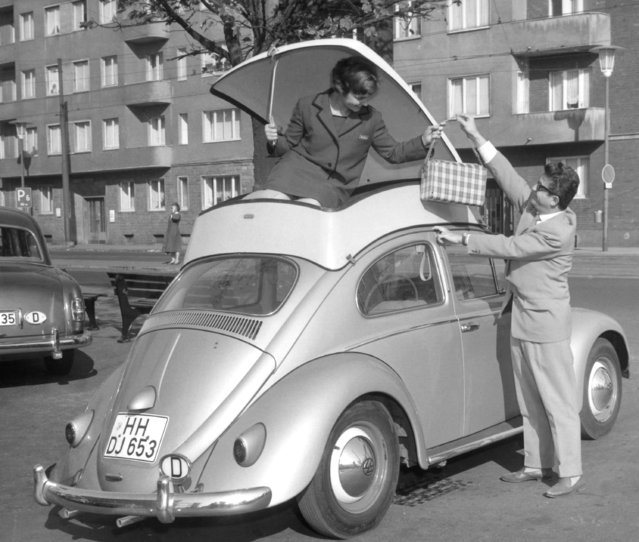 A young girl demonstrates the plastic container fitted to the roof of a Volkswagen Beetle car to provide extra luggage space around October 20, 1959. The case was on show at the International Plastics Fair in Dusseldorf, Germany. (Photo by Horst Faas/AP Photo)