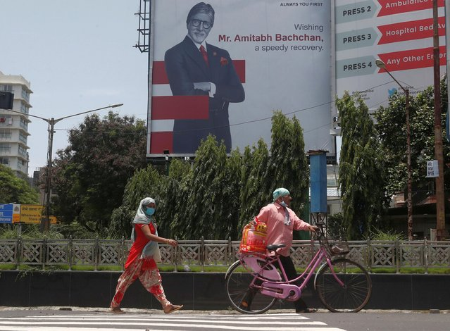 People wearing protective masks walk in front of a hoarding of Bollywood actor Amitabh Bachchan wishing him a speedy recovery, as he and members of his family were tested positive for coronavirus disease (COVID-19) in Mumbai, India, July 19, 2020. (Photo by Francis Mascarenhas/Reuters)