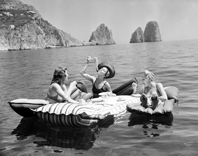 Unsettled life in Europe failed to change the slow pace of life on the Isle of Capri, off Naples, Italy. Some of the socialites who have come there to relax enjoy an aquatic luncheon serviced in the cool Mediterranean, September 1, 1939. Swimming waiters push out the floating tables bearing meals which include wine and spaghetti. In the background are the rocks of Faraglioni. (Photo by Hamilton Wright/AP Photo)