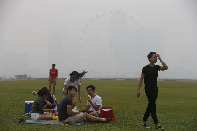 Youths have a picnic near the Singapore Flyer Observatory Wheel shrouded by haze in Singapore September 29, 2015. (Photo by Edgar Su/Reuters)