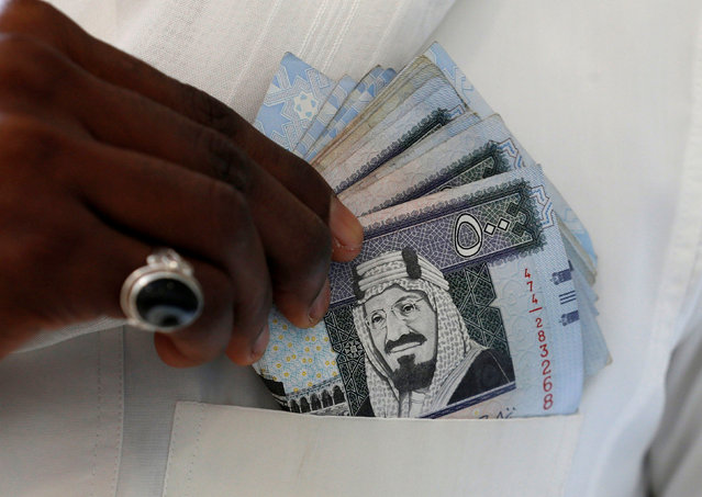 A Saudi man shows Saudi riyal banknotes at a money exchange shop, in Riyadh, Saudi Arabia January 20, 2016. (Photo by Faisal Al Nasser/Reuters)