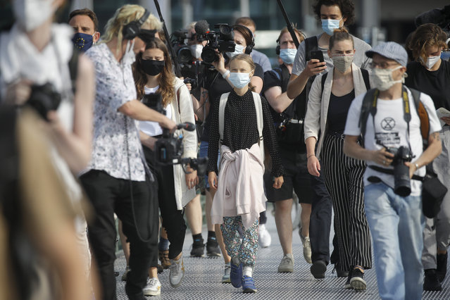 """Swedish founder of the """"School Strike for Climate"""" movement Greta Thunberg (C) wears a face mask as she walks to the Chancellery, where she was to meet the German Chancellor for talks on August 20, 2020. (Photo by Odd Andersen/AFP Photo)"""