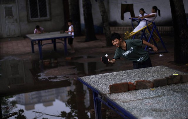 Chinese boys play ping pong in a hutong, or a traditional alleyway, of Beijing, China, Saturday, July 10, 2010. (Photo by Muhammed Muheisen/AP Photo)