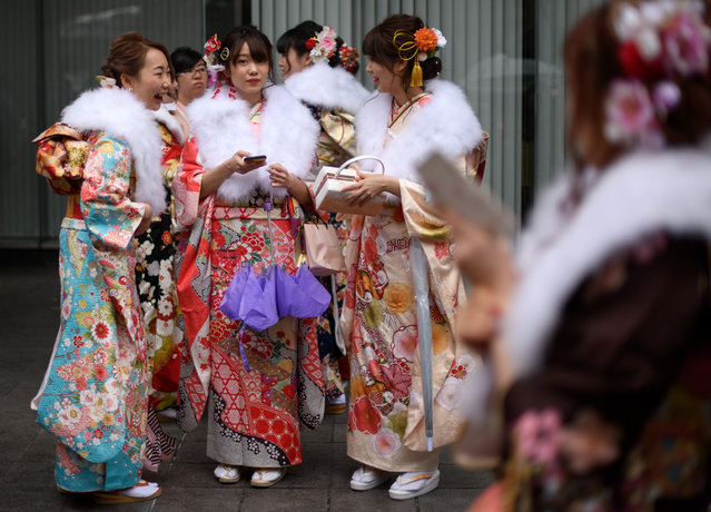Women wearing kimonos share a joke as a friend looks on as they gather after attending a Coming of Age ceremony on January 8, 2018 in Yokohama, Japan. (Photo by Carl Court/Getty Images)