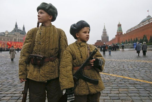 Boys dressed in historical uniforms stand before a military parade in Red Square in Moscow November 7, 2014. The parade marked the anniversary of the 1941 parade when Soviet soldiers marched through the Red Square towards the front lines of World War Two. (Photo by Maxim Shemetov/Reuters)