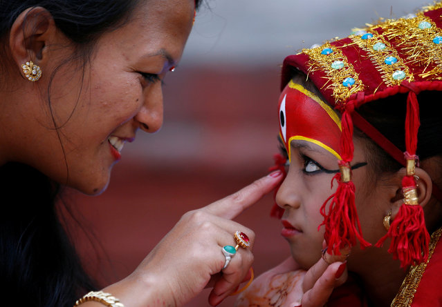 A woman smiles as she speaks to a young girl dressed as the Living Goddess Kumari during the Kumari Puja festival in Kathmandu, Nepal September 14, 2016. (Photo by Navesh Chitrakar/Reuters)