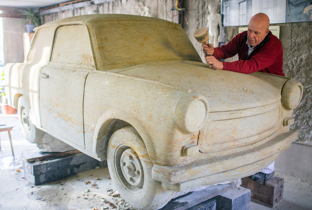 Sculptor and restorer Carlo Wloch works on a lifesize sculpture of a Trabant 601 car in his workshop in Berlin, November 7, 2014. After 6000 hours of work in 17 years Wloch created the car sculpture out of a huge block of sandstone. (Photo by Hannibal Hanschke/Reuters)