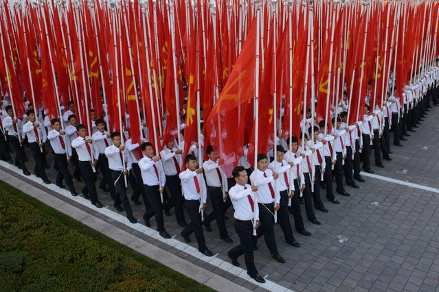 Participants hold flags as they pass through Kim Il-Sung square during a mass military parade in Pyongyang on October 10, 2015. (Photo by Ed Jones/AFP Photo)
