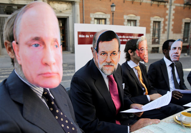 "(L-R) Protesters wearing masks depicting Russian President Vladimir Putin, Spain's Prime Minister Mariano Rajoy, European Commission President Jean Claude Juncker and U.S. President Barack Obama demand protection of the rights of refugees, migrants and displaced people, ahead of the world leaders meeting about the global refugee crisis next week, in front of Spain's foreign ministry in Madrid, Spain, September 16, 2016. The banner reads ""More then 17 persons die every day across the world trying to reach a dignified life"". (Photo by Andrea Comas/Reuters)"