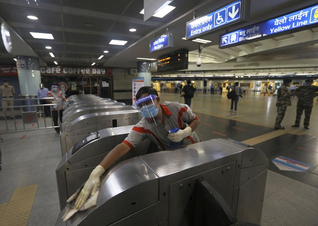 A workers sanitizes a metro station in New Delhi, India, Thursday, September 3, 2020. Delhi Metro will open its services in a phased manner from Sept. 7, even as India has been reporting the highest single-day caseload in the world every day for more than three weeks and is the third worst-hit country behind the United States and Brazil. The country's economy contracted by 23.9% in the April-June quarter, India's worst performance in at least 24 years. (Photo by Manish Swarup/AP Photo)